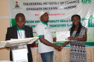 Mrs Tolu Falaiye presenting Certificate of Participation to an intern after the training
